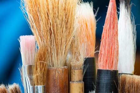 Artists paint brushes with blue background. Close up detail of the bristles. Mostly chinese watercolour brushes.