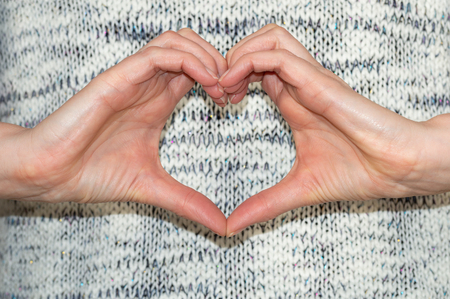 Woman in casual clothes making heart shape with hands in front of her body. Close up authentic style.