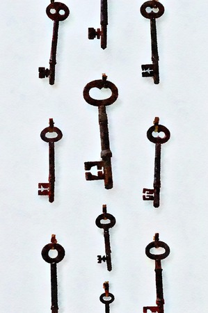 Watercolour painting of old rusty skeleton keys hanging on a white wall. Vertical.