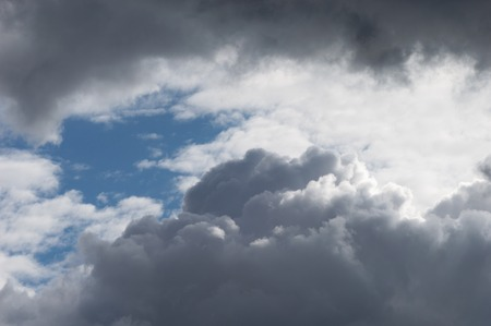 Billowing clouds with blue sky. Moody stormy weather with both grey clouds and contrasting brightly lit white clouds. Stock Photo
