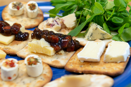 Crackers topped with a selection of cheeses, with sweet pickle and salad leaves. Close up view with focus on pickles. On a blue plate.