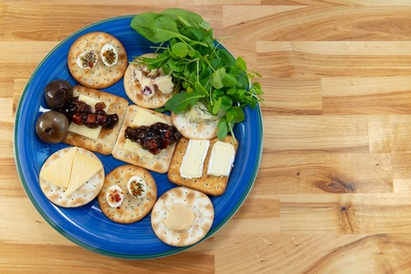 Crackers topped with a selection of cheeses, with pickles and salad leaves. On a blue plate on a wooden table. Viewed from above with copy spave to the right.