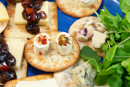 Crackers topped with a selection of cheeses, with sweet pickle and salad leaves. Close up view with focus on two oval shaped appetizer cheeses. On a blue plate.