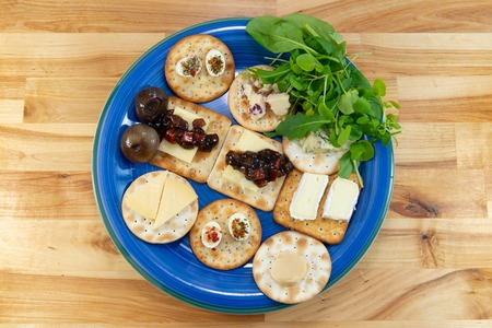 Crackers topped with a selection of cheeses, with pickles and salad leaves. On a blue plate on a wooden table. Viewed from above. Stock Photo