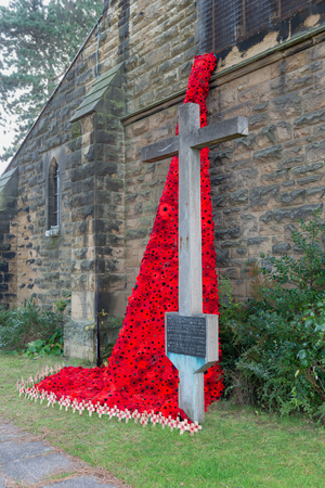 WREXHAM, UK - OCTOBER 31, 2018: Weeping Window poppy remembrance memorial and memorial cross for the missionary nurse Winifred Davies. St Tudfils church. Knitted poppies made by local residents.