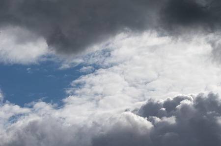 Stormy weather. Moody cloudscape with both dark grey clouds and contrasting brightly lit white clouds and blue sky.