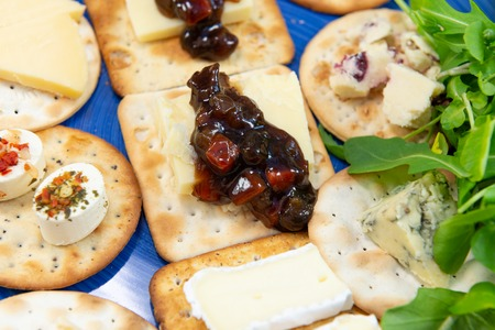 Crackers topped with a selection of cheeses, with sweet pickle and salad leaves. Close up view from above with focus on pickles. On a blue plate. Stock Photo