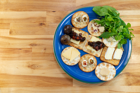 Crackers topped with a selection of cheeses, with pickles and salad leaves. On a blue plate on a wooden table. Viewed from above with copy spave to the left. Stock Photo