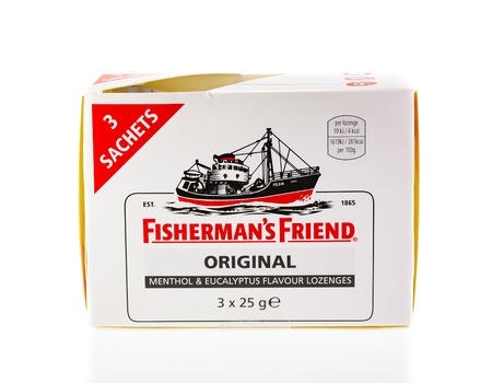 WREXHAM, UK - APRIL 01, 2017: Box of 3 sachets of Fishermans Friend, original flavour lozenges containing warming menthol and eucalyptus. The vapours when sucked are a remedy for common colds.