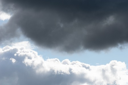 Billowing clouds with blue sky. Moody stormy weather with both oppressive dark grey clouds and contrasting brightly lit white clouds. Stock Photo