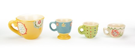 Four pretty ceramic teacups in a row on white background. Varying colours, patterns and sizes in descending order. Cheerful bright pastel colours. In a banner shape.