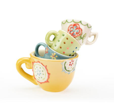 Four pretty ceramic teacups stacked in a wobbly unstable pile on white background. Varying colours, patterns and sizes. Cheerful bright pastel colours.