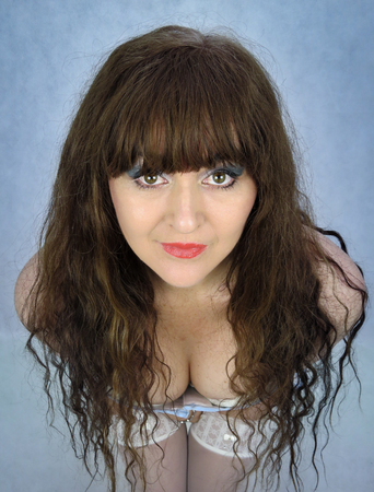 Attractive woman, portrait with long brown hair, showing cleavage. Viewed from above. Close up of face making eye contact, symmetrical pose. Subtle blue vignette.