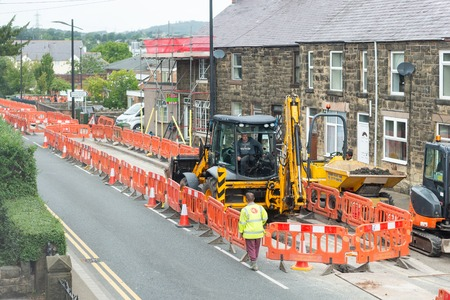 Wrexham, UK - August 24, 2017: Pipe laying roadworks in a Welsh village. Bright orange safety barriers and cones protect working area, with digger and workmen. Editorial