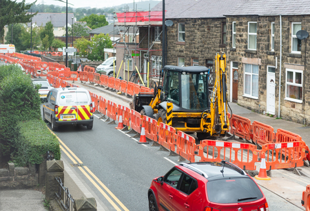 Wrexham, UK - August 24, 2017: Pipe laying roadworks in a Welsh village. Bright orange safety barriers and cones protect working area, with digger and passing traffic.