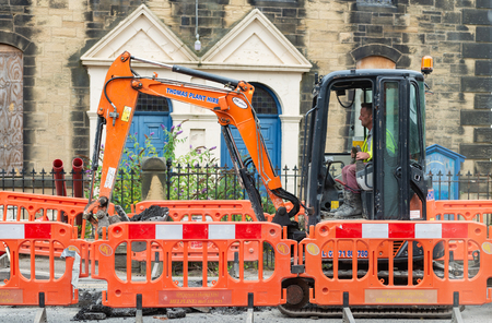 Wrexham, UK - August 25, 2017: Roadworks. Close up of workman operating digger on village street in front of a church. Bright orange safety barriers protect working area.