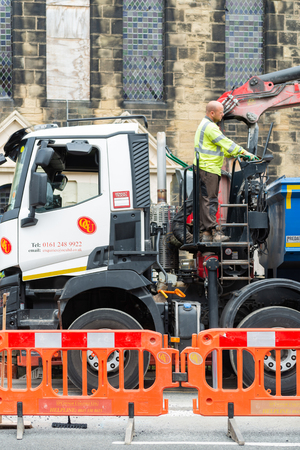 Wrexham, UK - August 25, 2017: Roadworks. Close up of workman standing on truck behind cab operating the heavy machinery. On village street in front of a church. Vertical. Editorial