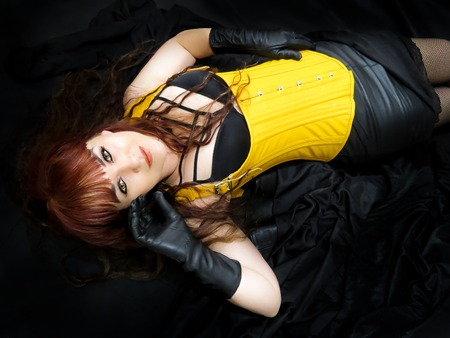 Attractive woman in yellow corset, lying down viewed from above. Black background. Imagens