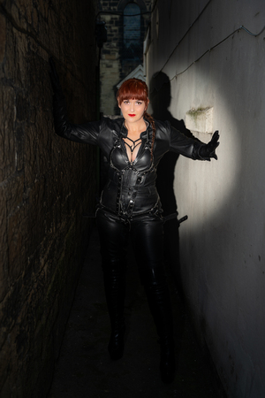 Creative effects applied to woman wearing black leather bondage jumpsuit in a dark alley at night, in a spotlight. Vertical.