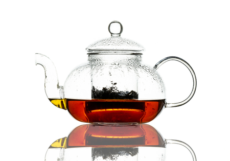 A single glass teapot containing brewing black tea, with tea leaves in the integral strainer. Isolated on a white background with reflection. High contrast black line lighting.