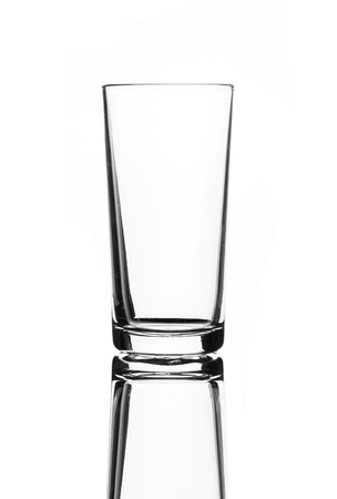 A single empty highball glass isolated on a white background with reflection. High contrast black and white, black line lighting.