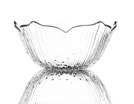 A single empty glass dessert bowl isolated on a white background with reflection. High contrast black and white, black line lighting. Stock Photo