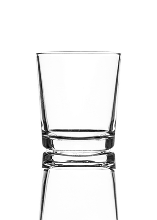 A single empty old fashioned glass isolated on a white background with reflection. High contrast black and white, black line lighting. Stock Photo