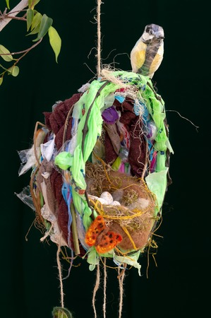 Recycled plastic waste hanging Great Tit bird sculpture on impressionistic nest with eggs and butterfly. Environmental impact of discarded waste materials on wildlife and nature concept.