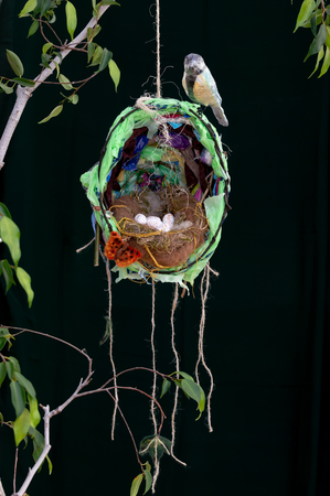 Recycled plastic waste Great Tit bird sculpture on impressionistic nest with eggs and butterfly. Hanging from branch. Environmental impact of discarded waste materials on wildlife and nature concept. Stock Photo