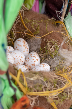 Garden bird nest sculpture. Ceramic Great Tit eggs in a felted sheeps wool nest. Vertical. Stock Photo