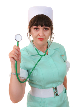 Female nurse holding up a stethoscope, looking forward making eye contact. White background. Vertical. Stock Photo
