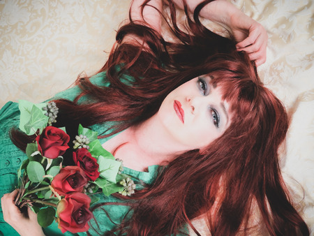 Woman with fiery red hair lies on pale damask background holding red roses, making eye contact. Creative filters applied. Close up.