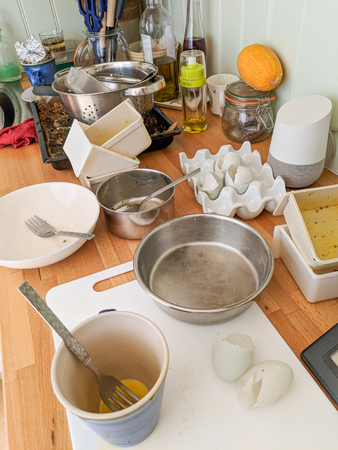 Wrexham, UK - June 26, 2018: Authentic messy domestic kitchen worktop with dirty dishes, broken eggshells, Google Home and other kitchen paraphernalia. Editorial