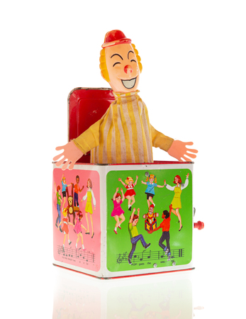 Wrexham, UK - July 02, 2018: Vintage toy clown Jack-in-the-box on a white background. Made by Hasbro in the 1970s. Pop goes the weasel song illustrated on box sides.