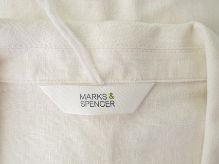 Wrexham, UK - June 07, 2018: Marks and Spencer womens clothing label on natural linen jacket collar. Close up of label. Editorial