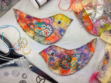 Process of hand made sewing project of a bird made with colourful felted fabric, cogs and embroidery embellishments.