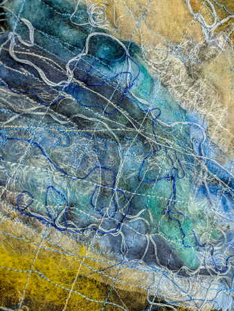 Hand made blue and yellow textured textile art background. Close up of random sewn detail.
