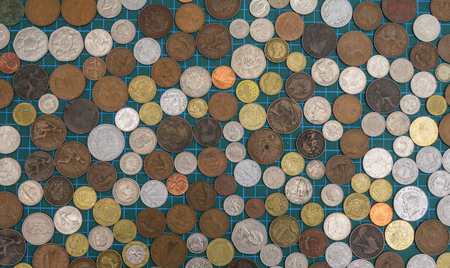Collection of old worldwide coins viewed from above. Variety of currencies, ages and metals. Diversity concept background. Stock Photo