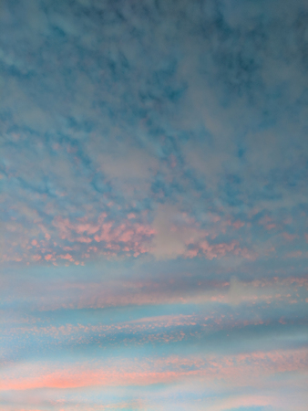 Pretty pastel pink clouds in a blue sky during a sunset in Wales UK. Vertical background or texture. Stock Photo