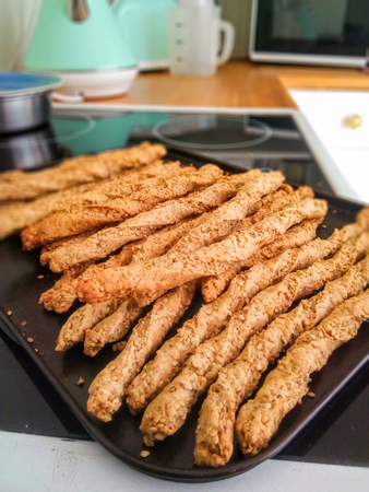 Authentic homemade twisted bread sticks on a baking tray in a kitchen. Vertical.
