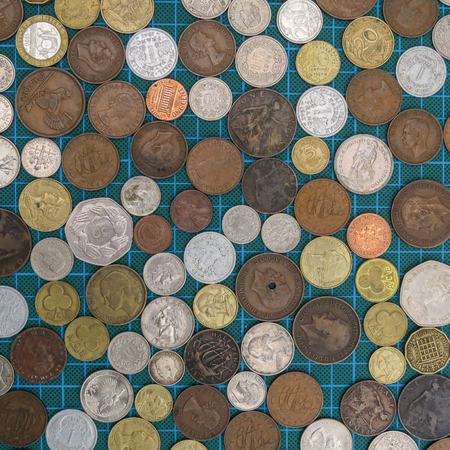 Collection of old worldwide coins viewed from above. Variety of currencies, ages and metals. Square background image. Diversity concept.