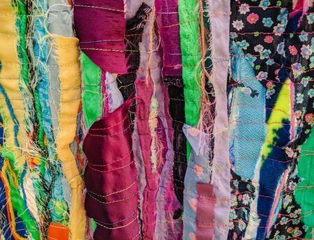 Colourful torn fabric strips, cords and wool, sewn together in a striped pattern. Textile art textured background.