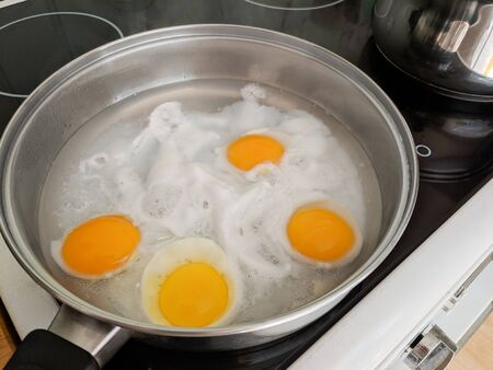Poaching fresh eggs in a pan of water in an authentic kitchen environment. Four eggs part way through being cooked. Stock Photo