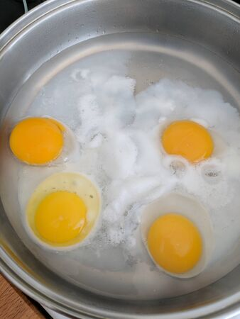 Poaching fresh eggs in a pan of water in an authentic kitchen environment. Four eggs part way through being cooked. Vertical.