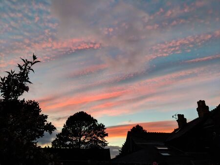 Colorful orange clouds in a blue sky during a sunset in Wales UK. Black silhouettes of trees and houses below.