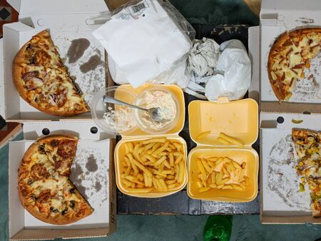 Overhead view of takeaway pizza meal partly eaten. Authentic home scene. Stock Photo