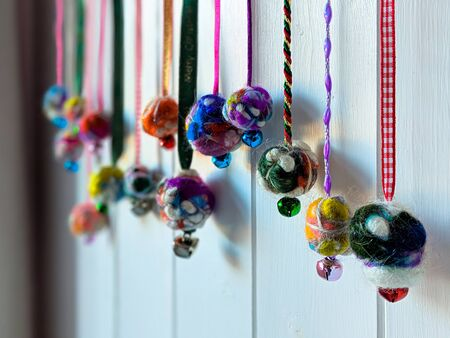 Homemade Christmas baubles hanging in a row. Made from colourful felted wool with ribbons and bells. Back lit with selective focus on white wooden background.