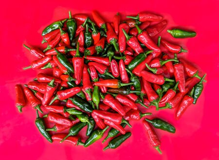 Red and green chilli peppers. Large fresh pile on a red background. Overhead view.