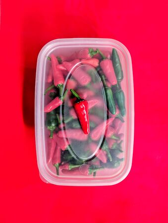 Red and green chilli peppers. Close up over head view of the freshly picked chillies in a plastic storage box. Red background.