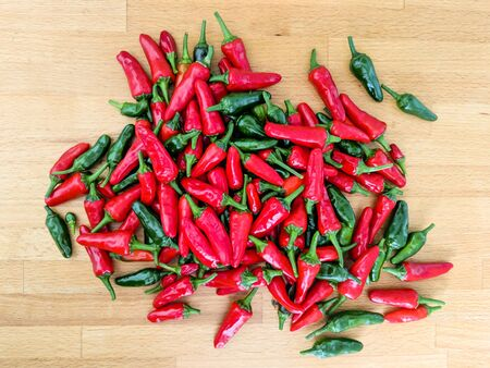 Red and green chilli peppers. Large fresh pile on a wooden kitchen worktop. Overhead view.